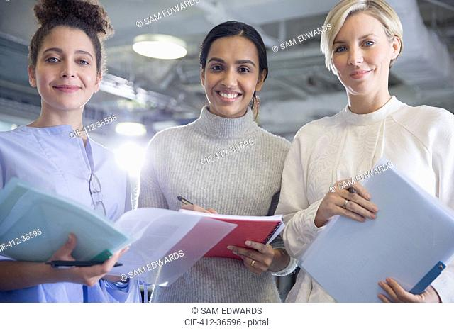 Portrait smiling, confident businesswoman with paperwork