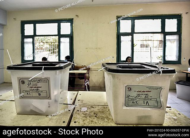 24 October 2020, Egypt, Giza: Electoral officials sit behind ballot boxes inside a polling station at Al Omrania district during the first round of the first...