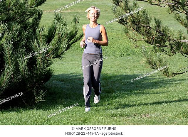 Blonde woman outdoors. Jogging in countryside