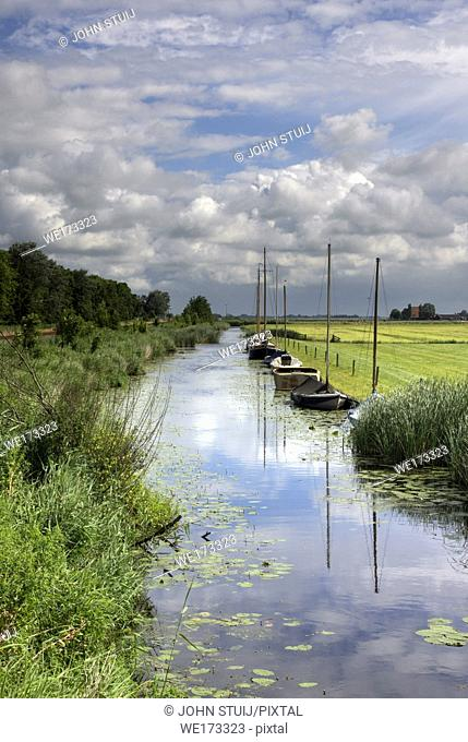 Moored sailing boats in a canal near the town of Workum in the Dutch province Friesland
