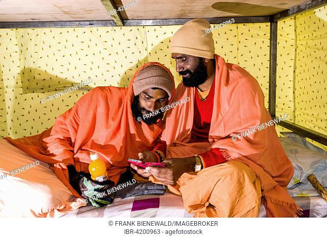 Two Sadhus, holy men, are playing with a smartphone in a tent, Kedarnath, Uttarakhand, India