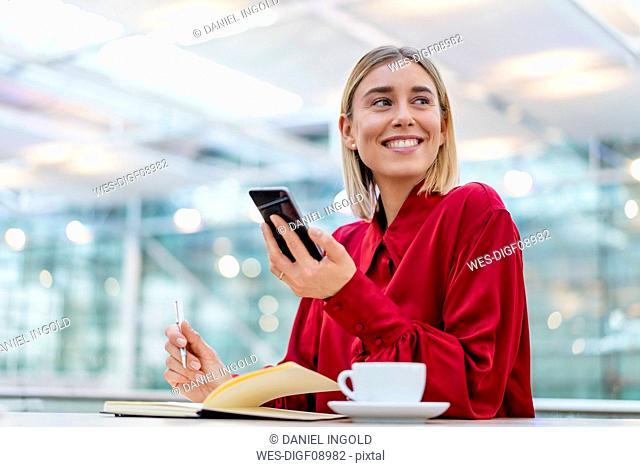 Young businesswoman with cell phone taking notes in a cafe