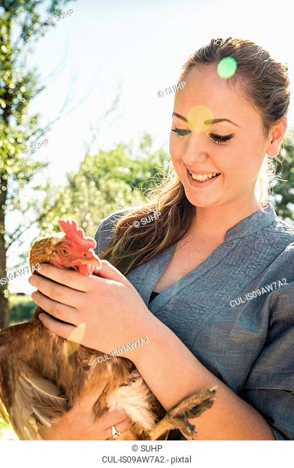 Woman holding chicken looking down smiling