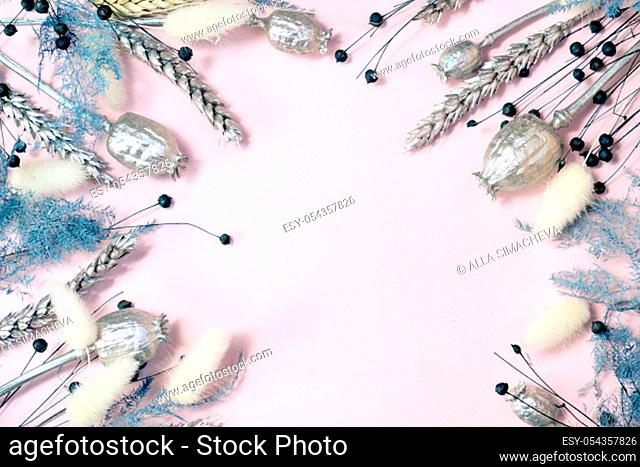 Flowers composition. Frame made of dried flowers on pastel pink background. Flat lay, top view, copy space