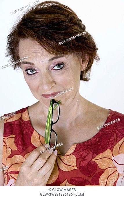 Portrait of a senior woman holding eyeglasses