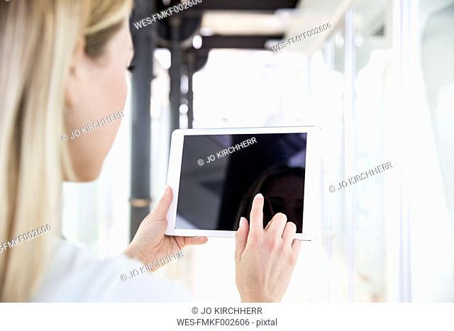 Young woman using digital tablet at dental surgery