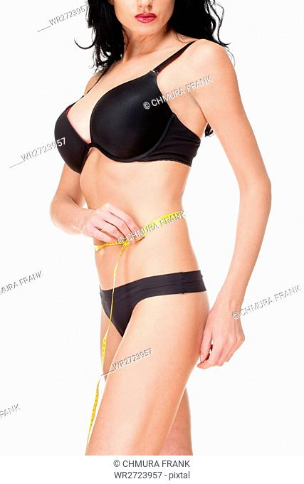 Woman in Black Underwear Measuring Results of Diet - Isolated on White