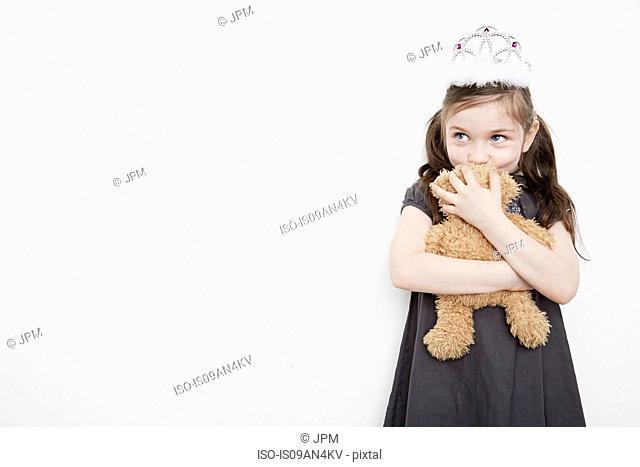 Girl wearing tiara holding teddy bear