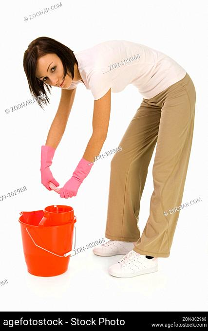 Young bent woman wringing washcloth to red bucket. Looking at camera, side view. White background