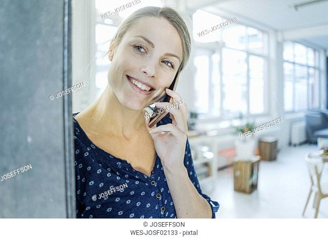 Portrait of happy young woman on the phone in a loft