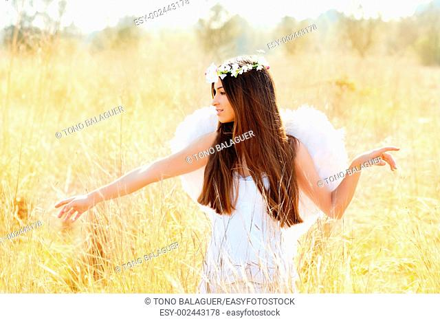 Angel etchnic woman in golden field with feather white wings and flowers crown