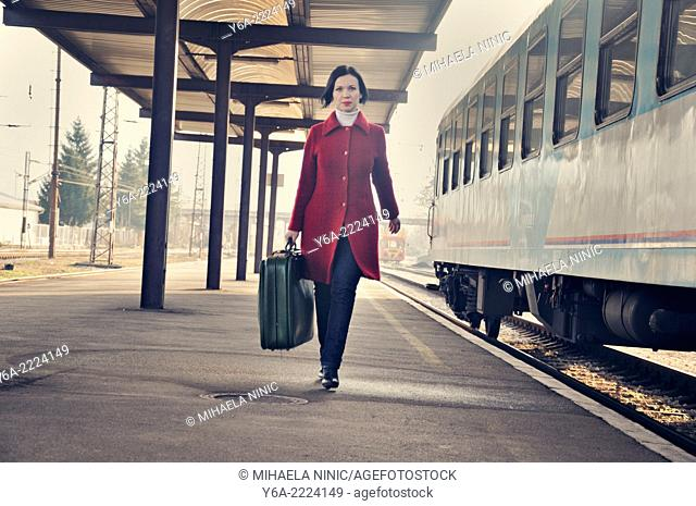 Woman carrying suitcase standing on railroad station platform, front view