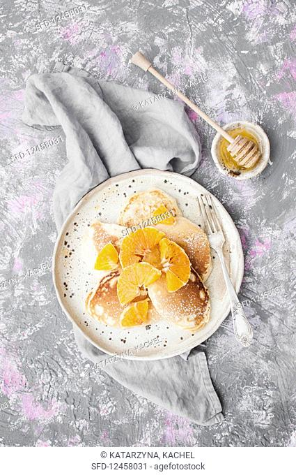 Pancakes served with oranges and honey