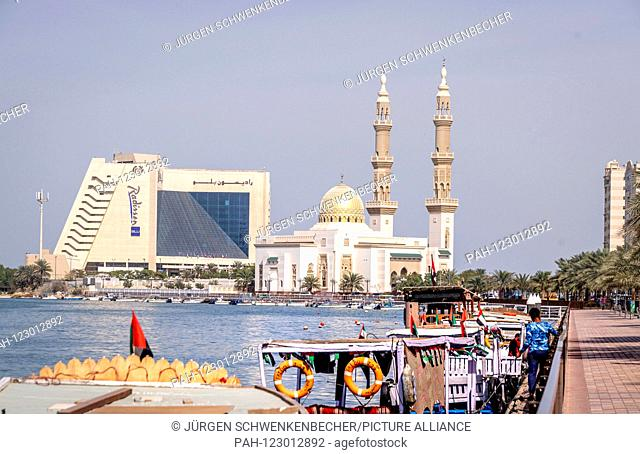 Tourist boats are waiting for customers at the Creek in downtown Sharjah. In the background you can see a hotel (Radisson Blu Resort) and a mosque (Al-Maghfirah...