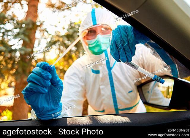Containment Scout vom Gesundheitsamt hält Rachenabstrich von Coronavirus Test in Drive-In Teststation