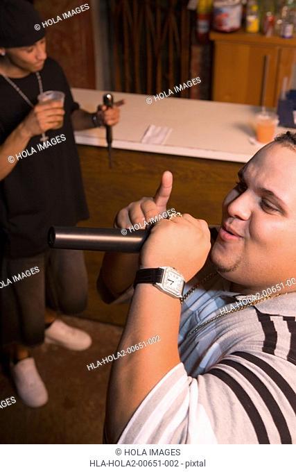 Young men singing at local bar
