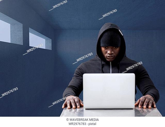 Hacker working on laptop in dark room