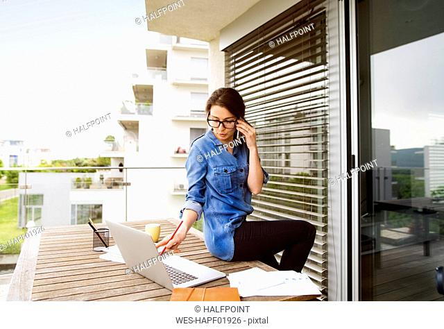 Businesswoman on the phone working on balcony at home