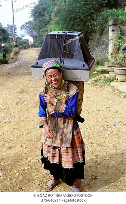 A flower Hmong woman on her way to the weekly market....with her TV set!!
