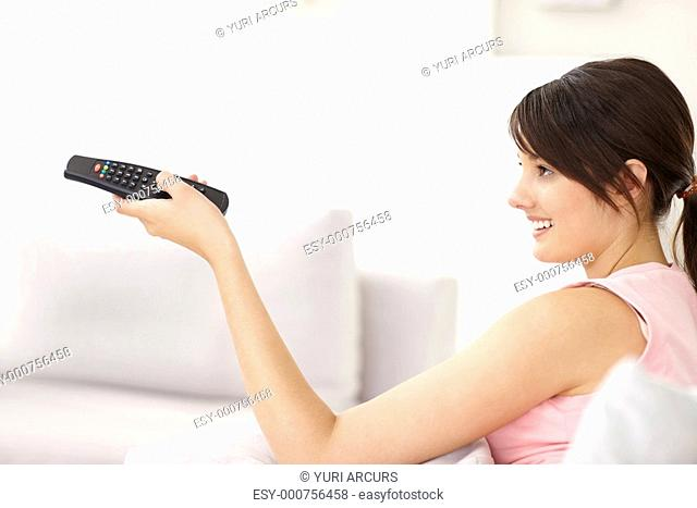 Cute female watching television , using a control to change the channels