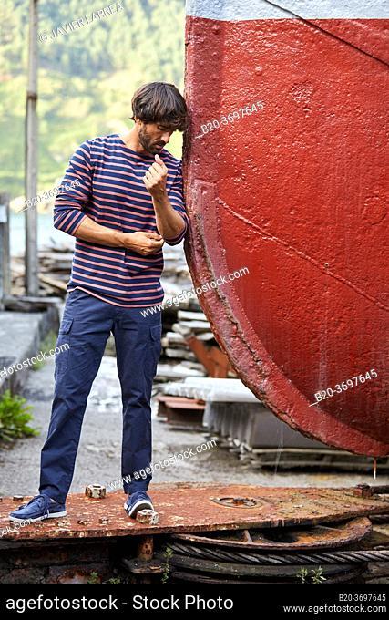 Young man walking in shipyard, ship in the port of Pasaia, Gipuzkoa, Basque Country, Spain, Europe