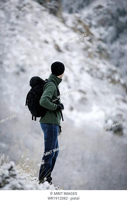A man wearing a fleece jacket and hat, carrying a rucksack, on a mountain slope