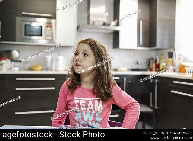 little girl painting a watercolor picture inside her house with the kitchen in the background