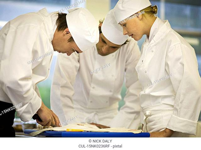 Three chefs filleting a fish