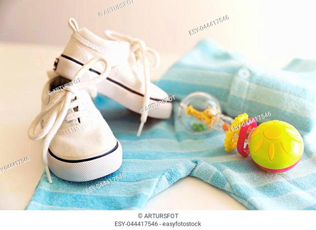 Baby stuff is on a white background. Things for little boy, rattle and shoes. Newborn baby necessities