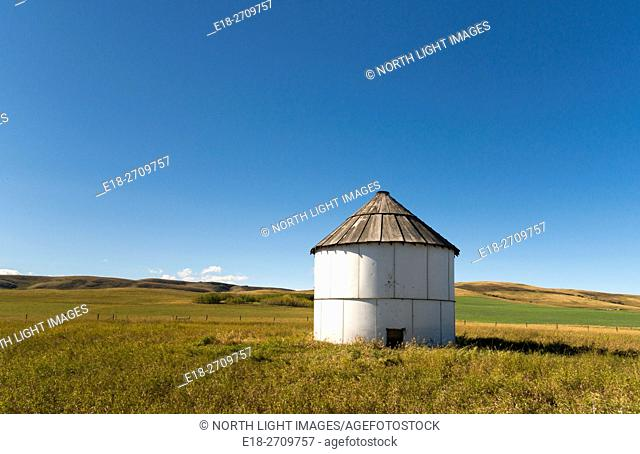 Alberta , Canada , Turner Valley. A single farm storage shed in the middle of a plain near the Rocky Mountains