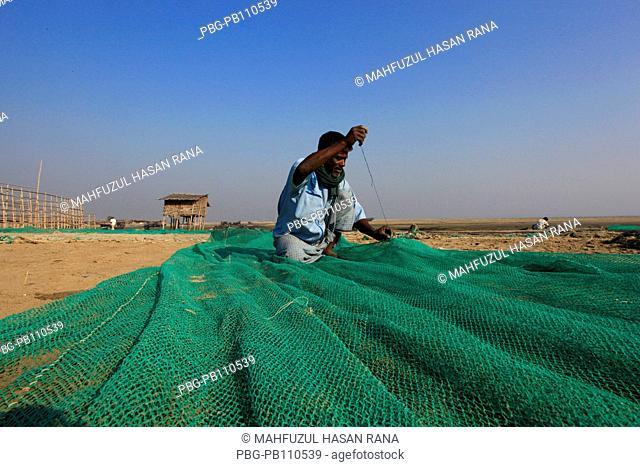 Fisherman repairs fishing net Cox's Bazar, Bangladesh February 2011