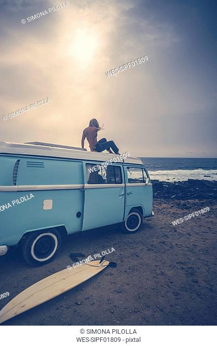 Young woman sitting on roof of a van on the beach