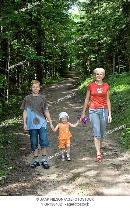 Young Woman With Kids, Family Walking Hand in Hand in Forest