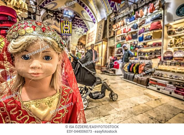 Unidentified Tourists visiting and shopping in the Grand Bazaar in Istanbul. Interior of the Grand Bazaar with doll in traditional Turkish clothes on the...