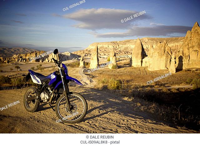 Motorcycle parked in front of pinnacle rock formations, Cappadocia, Anatolia, Turkey