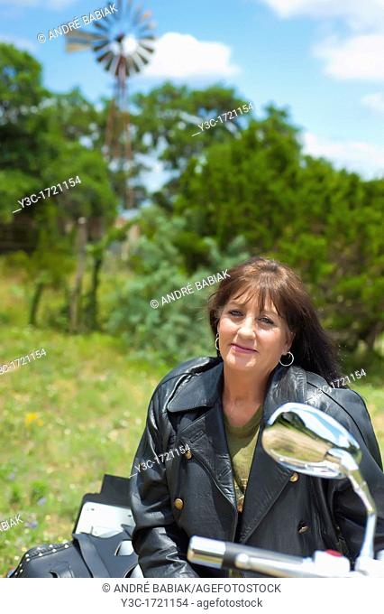 Biker Lady - Portrait of a mature Native American Woman in leather jacket with her motorcycle
