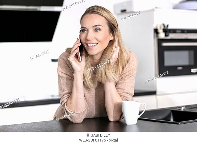Portrait of blond woman on the phone at home