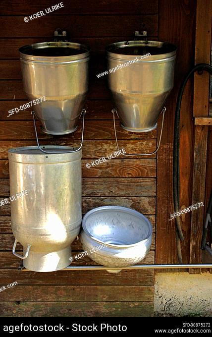 Milk cans on the wall of a wooden hut
