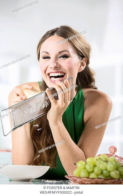 Germany, Young woman grating cheese, smiling