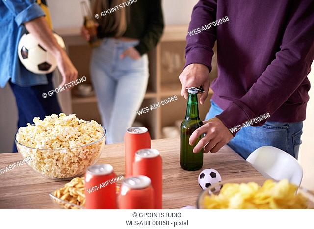 Football fan opening a bottle of beer