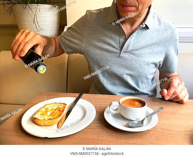 Man having Spanish breakfast, pouring olive oil on toast. Spain
