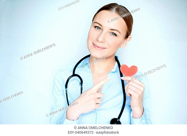 Portrait of a woman doctor with little red heart in hand isolated on blue clear background, cardiology clinic, conceptual photo of heart care
