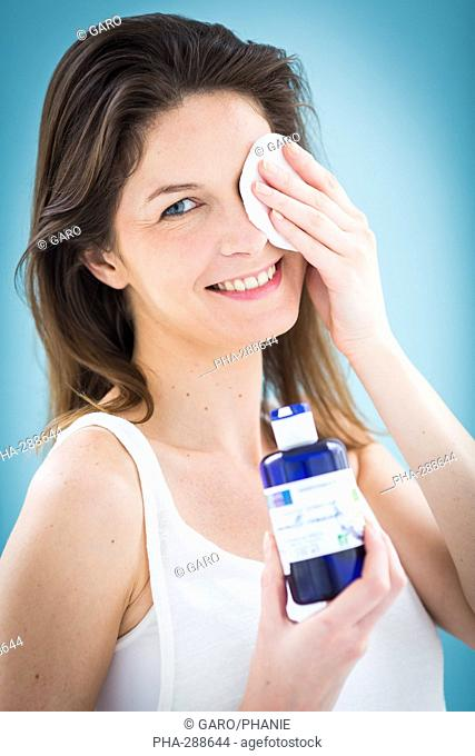 Woman applying a compress on the eyes with floral water