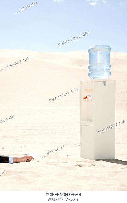 Person reaching for water cooler in desert