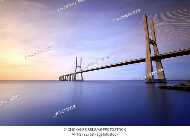 The colors of dawn on Vasco da Gama Bridge that spans the Tagus River in Parque das Nações Lisbon Portugal Europe