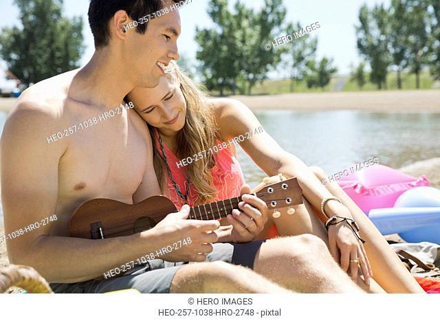 Man playing ukulele for woman on beach