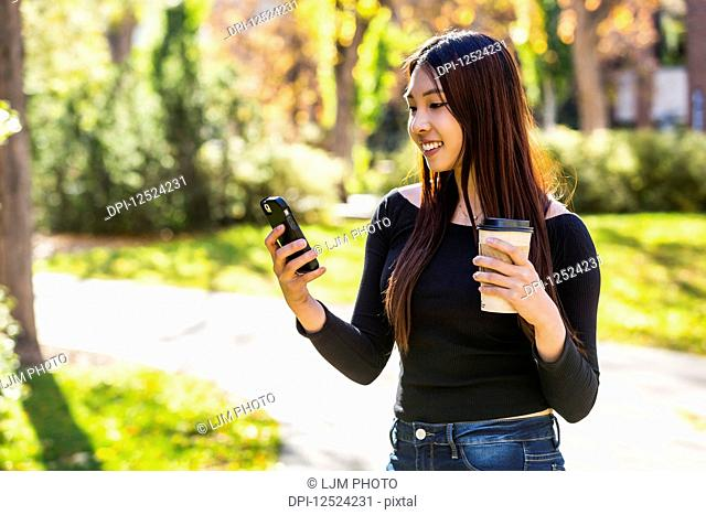 A young Chinese International student stands holding a coffee cup and using her smart phone on a university campus; Edmonton, Alberta, Canada