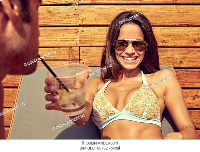 Hispanic couple sharing drink and sunbathing outdoors
