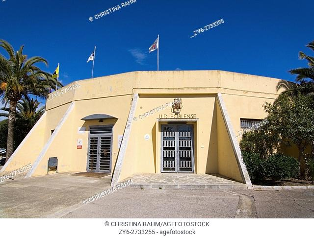 Sports club CD Poblense entrance building with flags, emblems and palm trees with blue sky in Sa Pobla, Mallorca, Balearic islands, Spain