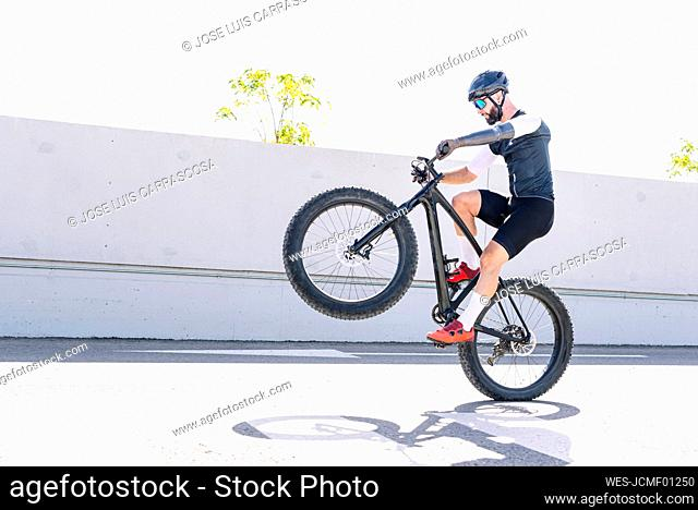 Male athlete with artificial limb performing stunt with bicycle on road against clear sky